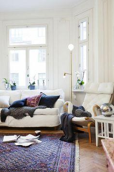 white living room, purple/blue, rug and pillows, white sofa, sheepskin, brass floor lamp