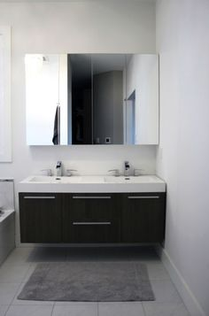 from Houzz: Two Ikea mirrored medicine cabinets are hung side by side above the floating vanity for a clutter-free aesthetic.