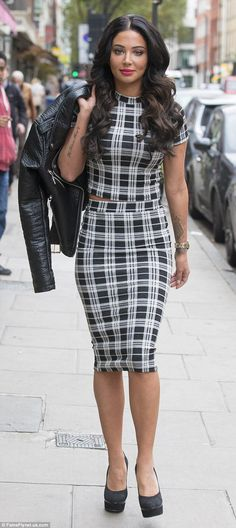Business chic: Tulisa flashed a hint of skin in her high-necked top and matching pencil skirt as she ventured out in London on Tuesday, just as the official lyric video for her single hit the internet
