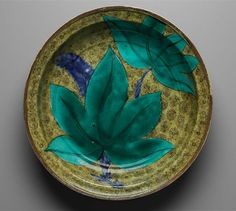 [Dish with decoration of tropical plant. Japanese, Edo period, 1650–1660. Ceramics: (12 5/8 x 2 5/8 in.) Arita ware in the Kutani style; porcelain with decoration in overglaze enamels and iron-oxide rim.