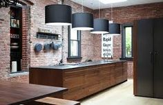 This Industrial-style kitchen features exposed brick walls, oversized drum pendant lighting, and a large kitchen island with black countertop and wooden drawer cabinetry. Industrial Kitchen Island, Industrial House, Industrial Interiors, Industrial Chic, Island Kitchen, Industrial Design, Kitchen Cabinets, Industrial Bookshelf, Industrial Windows