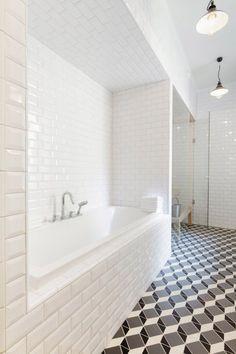 White shower tile and a graphic patterned floor