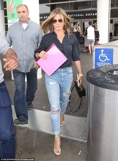 First class: The seemingly ageless beauty looked stylish in a navy blue button-up shirt, w...