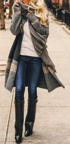 OVersized grey cardigan, white tee-shirt, blue skinny stretch jeans, black knee-high leather wedge boots. Latest arrivals 2015.