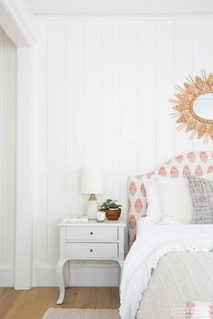 French meets Farmstyle in this sweet bedroom decor displaying shiplap walls, a pink block print headboard, and ruffled bedding.