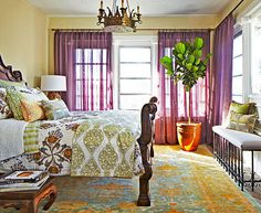 "Colorful John Robshaw bedding from Pioneer Linens motivated Shenaman to think outside the box when designing this bedroom. ""The carved bed complemented the character and feel of the linens, each evoking something old-world and soulful,"" she says. Her layered look overlaps two patterned area rugs atop wall-to-wall sea-grass floor covering, all from Stark Carpet. An iron bench offers seating with great outdoor views. www.traditionalhome.com"