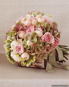 The palette for the bridal bouquet is more vivid, with pink garden roses (some barely budding, others full and layered like a tulle skirt), pink-tipped hydrangeas, and variegated geranium leaves, which add fullness.