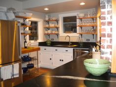 Updated 1895 Kitchen. Custom cabinets built by owner. Soapstone counters, open shelving. Small but efficient.