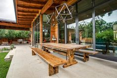 The home features a spacious patio with multiple seating areas, one being this outdoor dining spot with a rustic picnic-style table. Geometric pendants hang above the table, adding a contrasting punch of modern style.