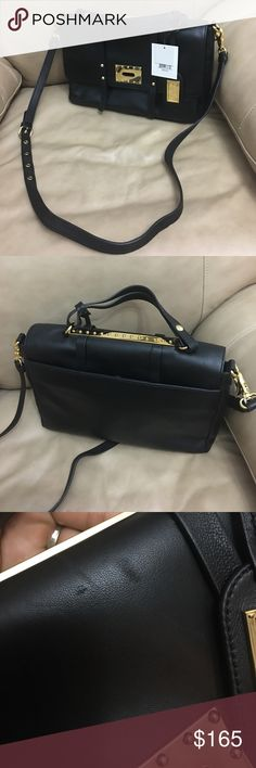 """Badgley Mischka Leather Turn-Lock Handbag, Black Badgley Mischka napa leather shoulder bag with golden hardware and stud accents. Adjustable strap with 23"""" drop. Top handle with 4"""" drop Flap top with tortoise turn-lock decorated with golden pyramid stud. Interior, logo print lining; one zip pocket. Exterior, removable hanging logo plate. 9""""H x 12""""W x 2"""" D; measurements are aproxímate   Comes with dust bag.. Longer Strap is removable.. can be worn as a Satchel bag or cross body.. 3rd pic…"""