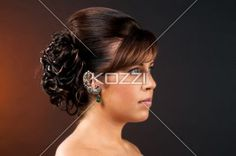 close-up shot of a young woman with elegant hairstyle. - Close-up shot of a attractive young female attractive hair bun and fringes over dark background. Model: Richelle Brown - Hair, MUA and Sylist: DMG Designz -  Jewellry Provided by Unique Rainbow