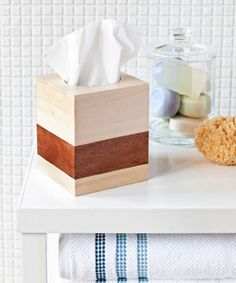 Disposable tissue box designs tend to (pardon the pun) blow. Here's how to DIY an attractive topper that'll last: Pick up an unfinished wooden tissue box, X-acto knife, wood veneer, decoupage glue (like Mod Podge), and polyurethane from a crafts store. Coat the box with polyurethane three times (follow product instructions). Cut four two-inch-wide strips of veneer, one to fit each side of the box. Glue on strips (ours are an inch from the bottom), coating both sides of each strip with glue…