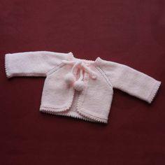 Abriguito de punto de lana con pompones, para bebé. Delantera.