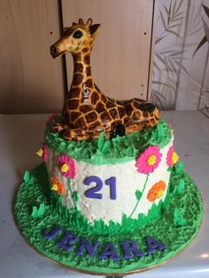Chocolate mud cake with buttercream icing, fondant giraffe and royal icing flowers and grass.