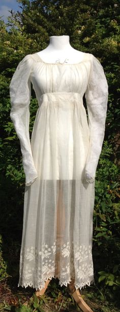 c1825 cream gauze gown. Fastens at back. Double band of shadow embroidery around hem.