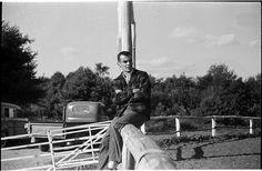 Leonard Bernstein [Unidentified man sitting on a fence.]