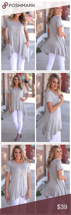 """🆕 Grey Asymmetrical Back Ruffle Tunic Super comfy grey tunic with cute back ruffle and pockets!!  Perfect weekend, beach, holiday top! 95% rayon and 5% spandex. Bust measurements flat: Small 22"""", Medium 23"""", Large 24"""". Length measurements: Small 29"""", Medium 30"""", Large 31"""". Bundle and save more! Tops Tunics"""