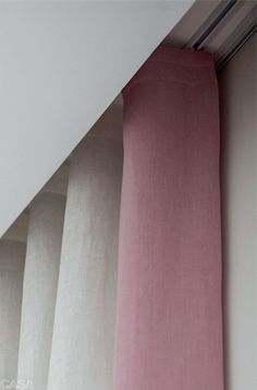 Emenda caprichada - As cambraias de linho rosa e branca são da Villa Nova Tecidos. Na emenda entre um tecido e o outro, há pespontos bordados a mão (Cara de Casa). Um forro de blecaute (Entreposto) cobre também a porta-balcão (4 x 2,80 m). Com leve ondulação, este modelo ganha o nome de serpentina. A moldura rosa mede 20 cm. O arraste da barra é de 3 cm.