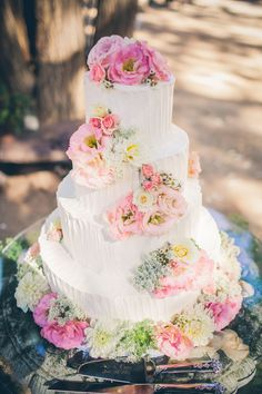 A buttercream cake was decorated with pink lisanthus, dahlias, queen anne's lace, wax flower and spray roses.