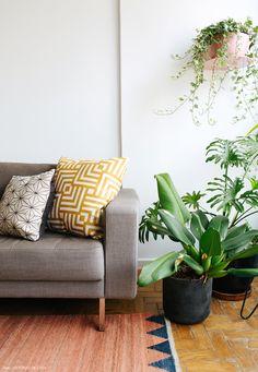 Sofá cinza, almofadas estampadas e plantas pendentes em vasos e suportes.