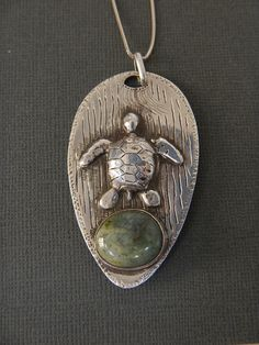 pendant sea turtle chased and repousse in sterling with sea stone.