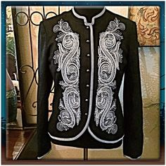 """Peter Nygard Wool Blend Jacket This is a gorgeous fully lined wool blend jacket that has light cream paisley stitching that flanks each side on the front. The standup collar & sleeve edges are trimmed in linear stitching. Pop it with a holiday red blouse or a silky cream one and pair w/ your best black pants, skirt, or jeans. Pretty textured metal round buttons down the center. Jacket can be left open or buttoned up. Measurements: Bust=39-40"""", Shoulder width seam to seam=16.5"""", Center back…"""