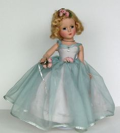 """Margaret Rose Bridesmaid   She's 14"""" tall, all hard plastic. She has the margaret face and her gown is blue shear over a satin bodice. The skirts are blue over pink. Roses in her hair, at the waist and on her wrist. She has a necklace of crystals and a cut crystal on the bodice. A really spectacular doll in mint condition. The gown was also made in all pink, blue or yellow.   Value: $800+"""
