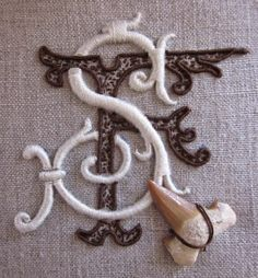Another beautiful monogram (S F) from Elisabetta ricami a mano. Love the combination of the satin stitch in white with the more textured seed stitch in brown.
