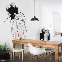 """Das Esszimmer ist ein Stilmix: Die Holzdielen und der Esstisch aus Holz geben dem Zimmer eine natürliche Atmosphäre, während die Designerstühle und die Hängeleuchte modern wirken. Als Wandschmuck ist hier das Wandtattoo """"Model"""" von Pixers zu sehen. - mehr auf roomido.com"""