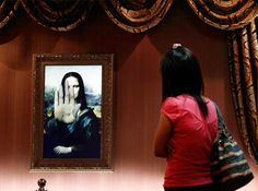 """A visitor looks at a three-dimensional, holographic version of the 16th century portrait """"Mona Lisa"""" by Leonardo da Vinci as it indicates not to move any closer in Beijing's Alive Gallery.(Reuters)"""
