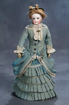 French bisque poupee, circa 1875. Wearing an aqua and ivory walking suit,undergarments,stockings,shoes,bonnet,earrings,brooch with lorgnette.