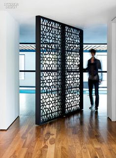 A custom screen in laser-cut, powder-coated steel pivots 360 degrees   http://www.interiordesign.net/projects/detail/2397-turning-point-minimal-toronto-house-by-paul-raff/