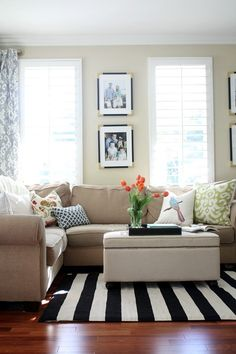 Grounding a room with a rug is a great way to add style to your decor. This black and white striped rug adds a fun statement to this family room, and also picks up the black in the picture frames and ottoman tray, tying it all together!