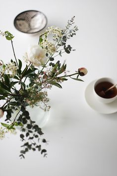 i like the clean / crisp feel of this photograph .... simple pleasure of a cup of honey with the old school wood honey spoon... beautiful flowers that look like they came from the garden and the out of focus morrocan (?) ceramic whoch suggests travel &  an appreciation for handmade things