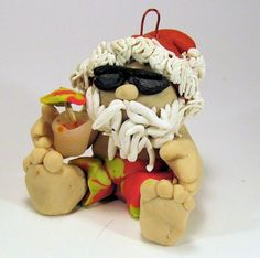 Tropical beach Santa ornament made of polymer clay. Cool off with a umbrella drink