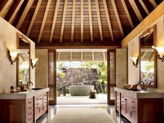 The master bath opens onto the shower garden in a pavilion-style residence designed by Shay Zak on Hawaii's Kona coast.