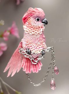 Julia Gorin Moluccan Cockatoo Brooch, created of silk and cotton and micro sequins. Metal fittings and chain are rhodium plated, with two pink Swarovski briolette crystals hanging down.