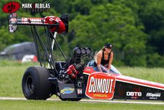 NHRA top fuel driver Leah Pritchett rides up the return road in the cockpit of her Gumout dragster..