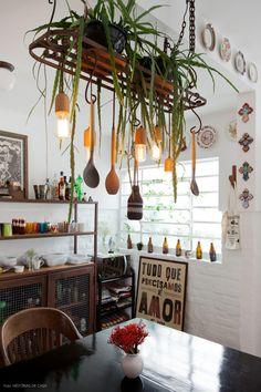 Uma antiga grade serve como suporte para as plantas e pendente na cozinha dessa casa de vila.
