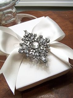 pretty rhinestone pin used to glam up a simple white box, tied with wide satin ribbon