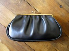 Vintage 60s faux leather clutch bag with chain for use as a handbag. Small size with a gathered front, gold kiss lock clasp, piping around the