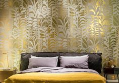 Golden leaf patterned design wallpaper that looks absolutely stunning over a yellow blanket tucked under a layer of black and gray textiles.