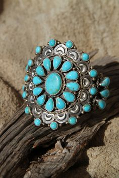 A traditional Navajo Indian Turquoise cluster cuff bracelet with beautiful repousse stamping on the heavy sterling silver cuff bracelet. Signed DB.