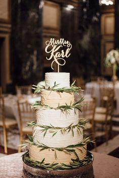 white and gold wedding cake with greenery