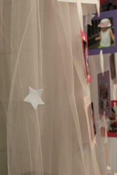 A mamãe da Manuela fez um móbile de fotos e pendurou um véu com estrelas em feltro