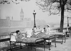 Tuberculosis patients from St. Thomas' Hospital rest in their beds in the open air by the River Thames, opposite the Houses of Parliament, in May 1936