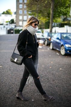 Emma Hill wears oversized grey scarf, Celine Box bag, black chunky sweater, black skinny ripped knee jeans, grey bow ankle boots, chic autumn winter all black outfit