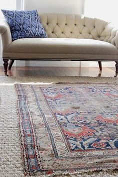 Antique rug over sisal, and that happy ikat pillow on the sunny loveseat