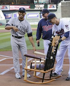 "New York Yankees pitcher Mariano Rivera, left, reacts to the ""rocking chair of broken dreams"" made up of broken bats which was presented to him by Minnesota Twins manager Ron Gardenhire and Twins players, including Justin Morneau, right, before a baseball game, Tuesday, July 2, 2013, in Minneapolis. (AP Photo/Jim Mone)"