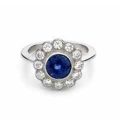 A sapphire and diamond cluster ring, the circular sapphire of 2.12cts within a border of old-cut diamonds, approximate combined weight 0.75ct, mounted in an 18ct white gold rubover setting.
